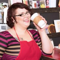 Ginger-haired fatty Kitten McPherson sports short hair and glasses while getting naked in a cafe setting