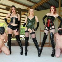 Dominant chicks manhandle male subs with strap-on cocks while in latex garments and boots