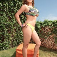 Solo model Valory Irene poses in an outdoor garden setting in a brassiere and thong