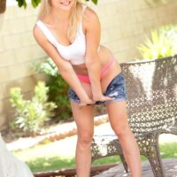 Uber-cute blonde teenager Mindy unsheathes her hard breasts with her bum garmented  in a g-string on a patio