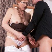 Grannie in glasses seduces a younger boy before fellating his cock on a chesterfield