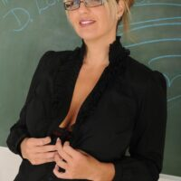 Elderly yellow-haired dame clad in glasses strips naked in front of a chalkboard in a classroom