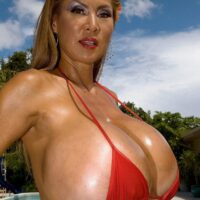 Buxom Asian doll Minka models a pair bikinis outdoors in close intimacy to a pool