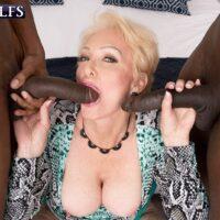 Tempting ash-blonde granny Seka Black fellates a pair of large ebony penises during MMF sex