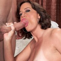 Brunette cougar Ruby Thompson sucks on the ball sac while giving her toy boy a blowjob