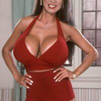 Asian XXX actress Minka freeing large tits from a crimson sundress in high heels